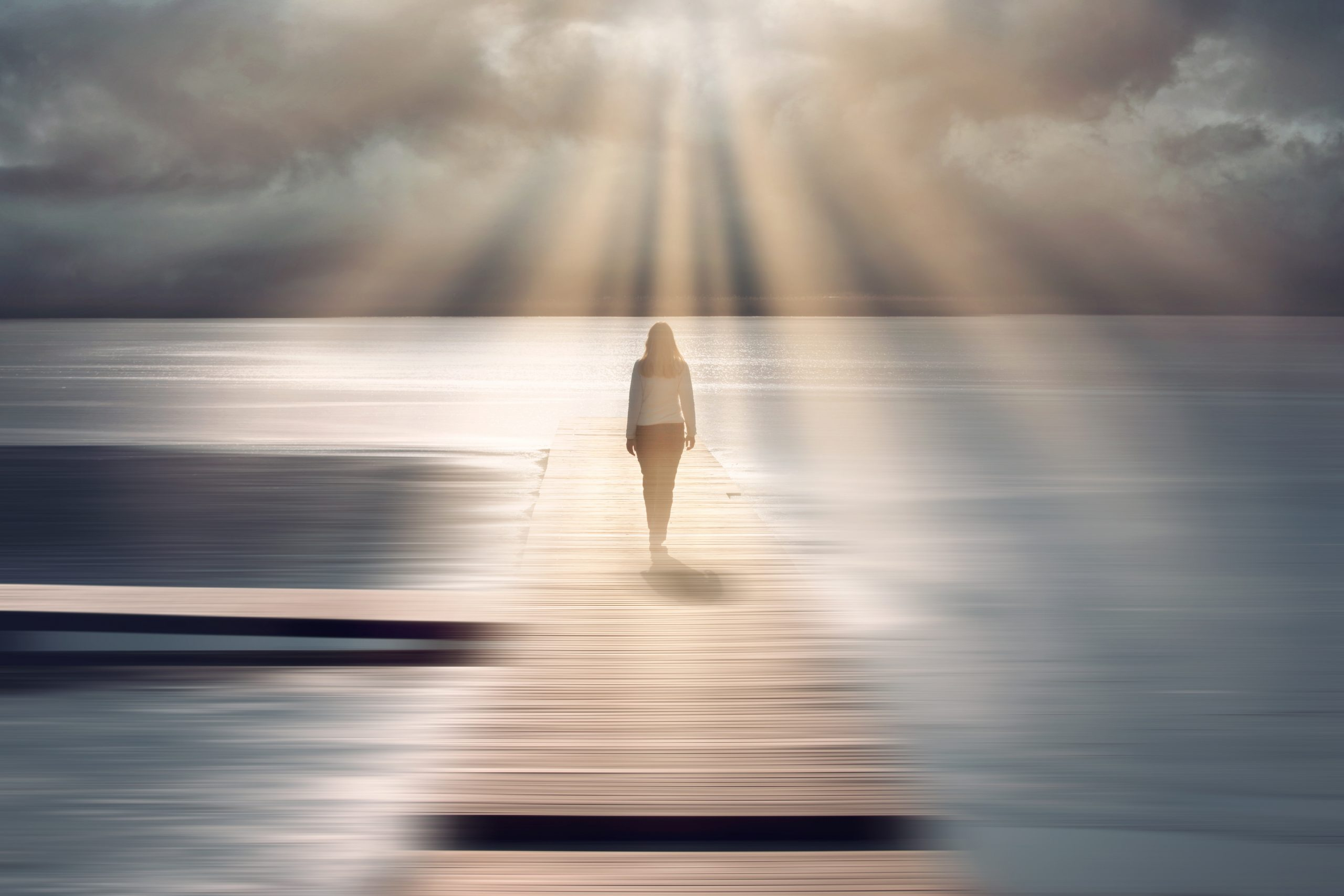 Spiritual sunny light with beams and back view of a walking woman.